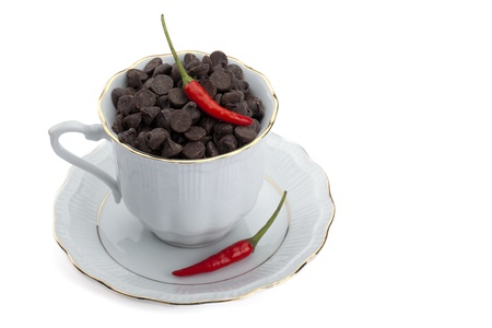 semisweet: Chocolate chips and hot chili pepper on a cup with saucer Stock Photo