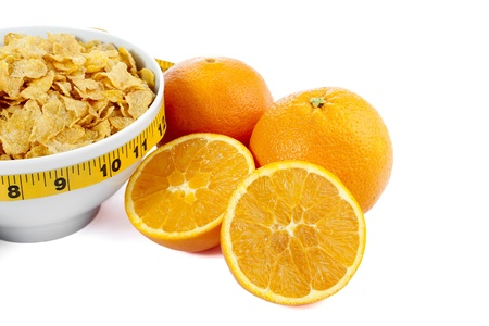 A close up image of a cropped corn flakes bowl with orange fruit on the side isolated on Stock Photo - 16998684