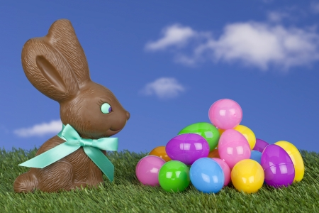 Cute chocolate bunny with eggs made of candy laid in grass under a blue sky