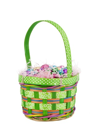elliptic: Portrait of small green basket with Easter eggs and chocolate over the white background