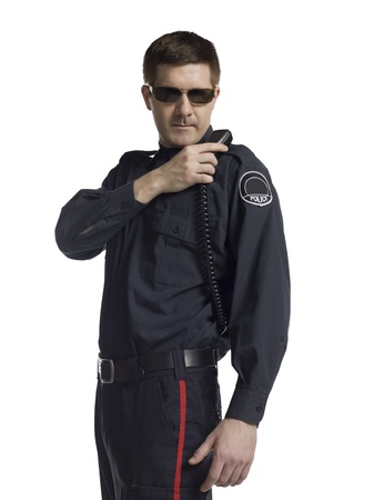 deputy: Mid-adult policeman holding the radio over his shoulder Stock Photo