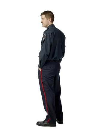 Back view image of a police officer with hands inside the pocket against the white background photo