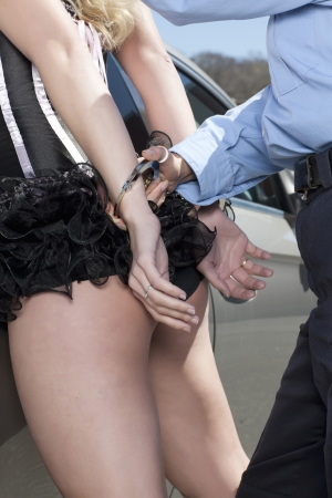 Close-up image of a police woman putting handcuffs to the arrested sexy woman Stock Photo - 16998767