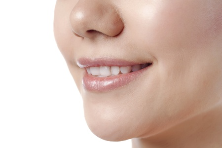 Close-up image of smiling lips of a woman isolated on a white background