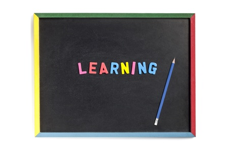 slateboard: Close-up shot of an empty slate with plastic alphabets forming learning with sharp blue pencil on it. Stock Photo