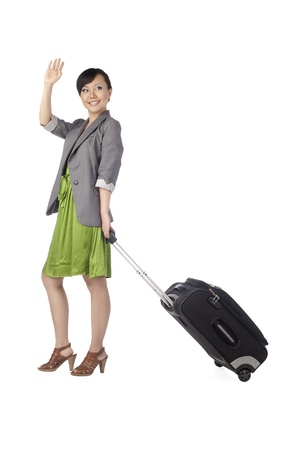 Portrait of a female traveler waving her hand showing goodbye photo