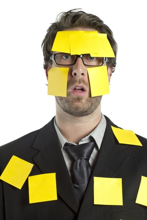 Portrait of stressed businessman covered by sticky notes against the white background photo