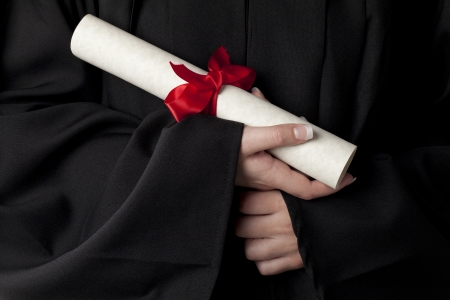 woman's: Close-up image of womans hand holding a graduation diploma Stock Photo