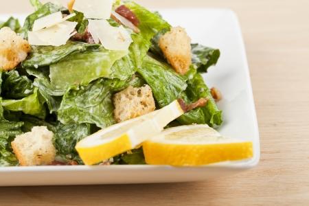 ensalada cesar: Cerrado disparó de apetitoso plato de guarnición de ensalada césar con rodajas de limón