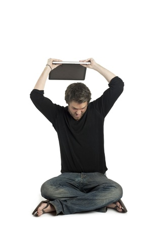 Close-up image of a stressed man about to throw his laptop on a white surface photo