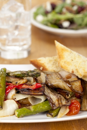 panino: Close-up image of plate with grilled vegetables topped with toasted bread on a wooden table