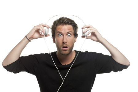 Close-up image of shocked man with headphone while listening to the music