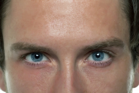 Close-up image of a blue eyed man looking at the camera