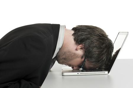 delusion: Portrait of burnout businessman with a laptop against white background