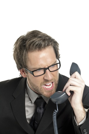 Close-up image of businessman angry talking on the phone against the white surface photo