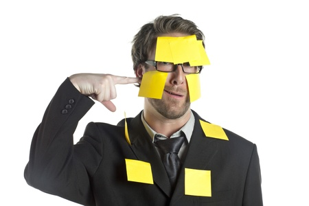 Close-up image of businessman with his finger on the cheek covered with sticky notes photo