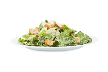green salad: Close up image of delicious ceasar salad in white plate against white background