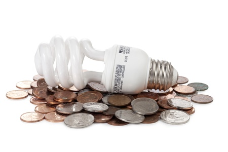 conserving: Close-up image of a light bulb lying on the coins against the white background Stock Photo