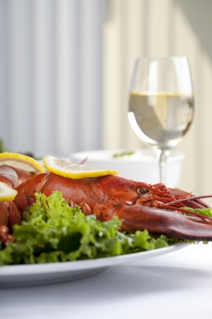 Close up image of lobster in white plate with lemon slice and white wine photo