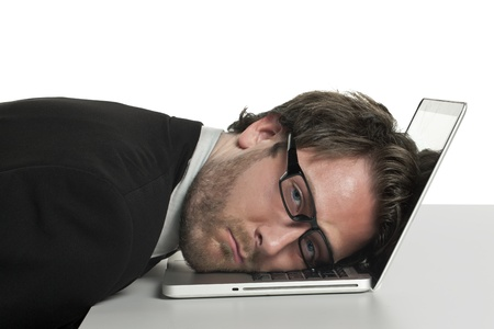 Closed up portrait of a tired businessman leaning on his laptop