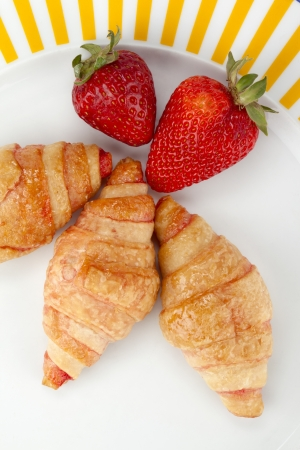 Plate of yummy croissant rolls with strawberry