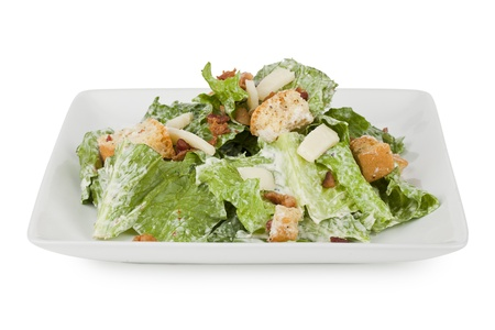 croutons: Yummy serving of Caesar salad on platter isolated in a white background Stock Photo
