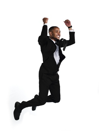 only mid adult men: Side view of a happy businessman jumping in air over white background. Model: Kareem Duhaney