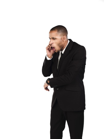 Angry businessman shouting on cellphone over white background,  Model: Kareem Duhaney photo