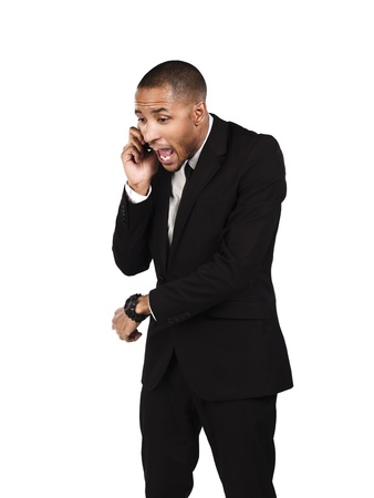 Angry businessman shouting on mobile phone against white background, Model: Kareem Duhaney photo