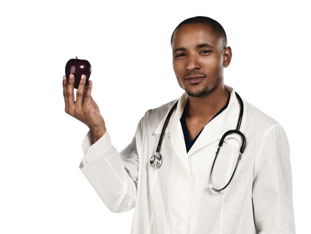 Confident young doctor holding an apple over white background, Model: Kareem Duhaney Stock Photo - 17111141