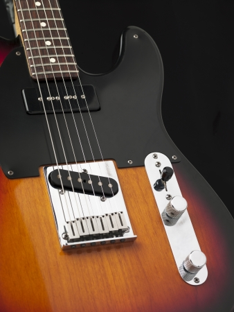 Close-up cropped shot of a electric guitar with metal strings and volume knobs against dark background. Stock Photo - 17100959