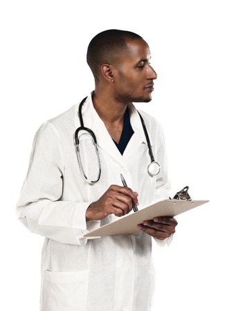 Doctor looking away while making notes over white background, Model: Kareem Duhaney Stock Photo - 17100715