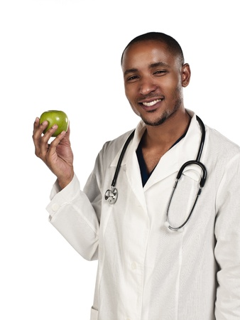 Happy young doctor holding green apple against white background, Model: Kareem Duhaney Stock Photo - 17111439