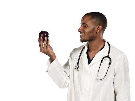 Happy young doctor looking at an apple against white background, Model: Kareem Duhaney Stock Photo - 17110647