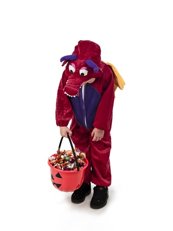 goodies: Boy wearing halloween costume  looking at bucket full of goodies. Stock Photo