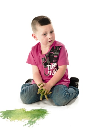 Small kid showing disgust with the mess of paint on his hand. Stock Photo - 17110665