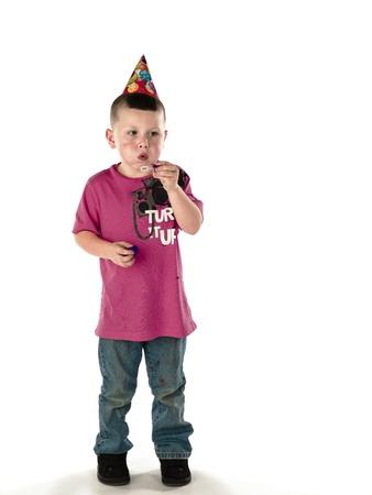 Little boy wearing party hat blows bubble wand.