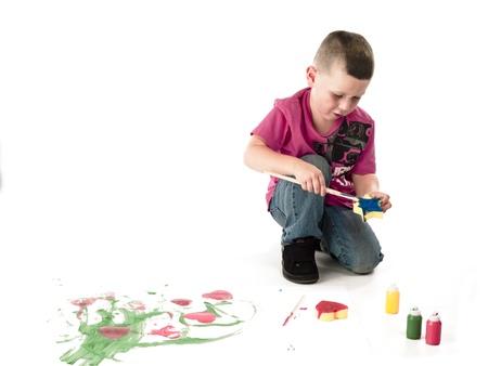 Little boy painting star shaped foam blue using an acrylic paint. Banco de Imagens
