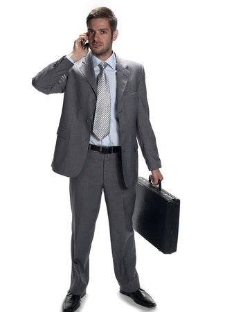 Businessman on a cell phone while holding a breifcase. photo