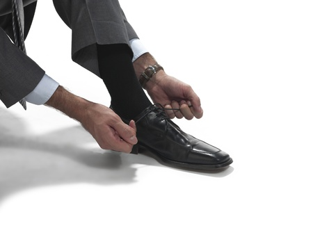 crouches: Man crouches to tie dress shoes