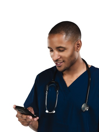 Nurse looking at phone and smiling, with white background.  Model: Kareem Duhaney photo