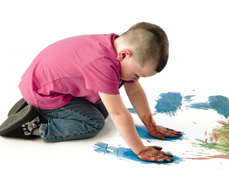 Little boy using his tiny hands to hand paint on a white card board. Stock Photo - 17100708