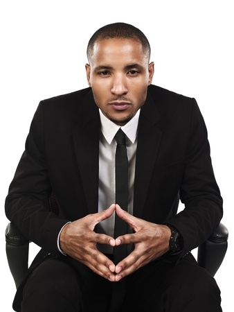 Portrait of a serious businessman sitting on a chair, Model: Kareem Duhaney photo