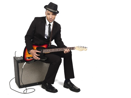 Portrait of a young businessman playing guitar while sitting on amplifier, Model: Kareem Duhaney Stock Photo - 17110219