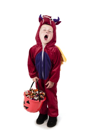 treating: Kid yawning after trick or treating in neighborhood.