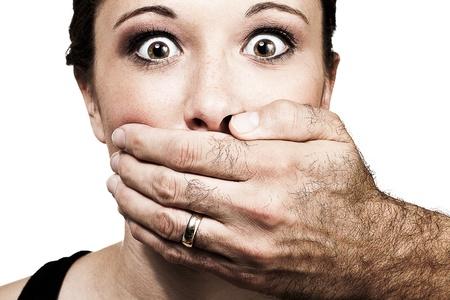 imbavagliare: La mano di un uomo tiene il volto di una giovane donna, il suo prefenting di parlare come lei stelle nella fotocamera con orrore. Archivio Fotografico