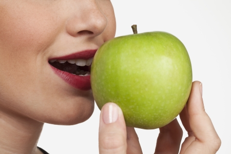 The apple is emphasised in the closeup studio shot of a women about to bite into an fresh apple. Stock Photo - 17101196