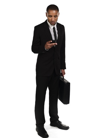Young African American businessman  text messaging against white background, Model: Kareem Duhaney Stock Photo - 17110070