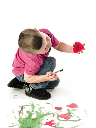 canvass: Ni�o peque�o inspeccionar espuma en forma de coraz�n despu�s de que �l la presion� sobre el lienzo.