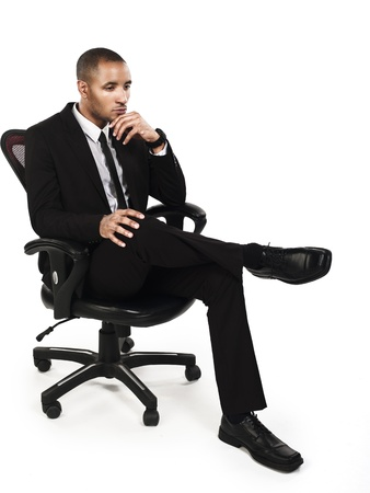 Young businessman contemplating while sitting on chair, Model: Kareem Duhaney photo